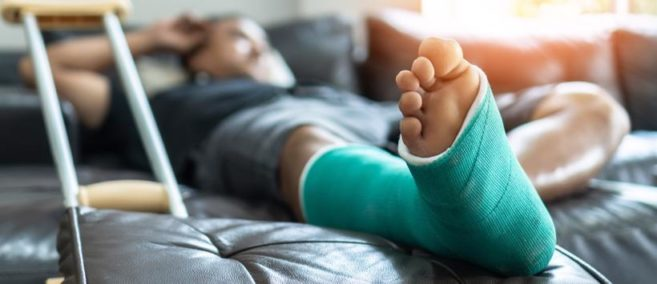 A man laying in bed with a injured foot in Greenville, SC