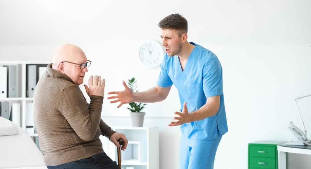 A male nurse yelling at an elderly man.